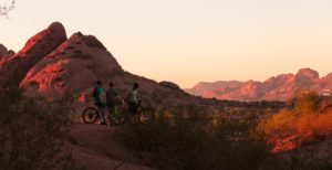3 people riding bikes at sunset with mountains in the background and red rock all around while on a mountain bike tour.