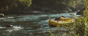 Rafts tied up along shoreline with water rushing and trees