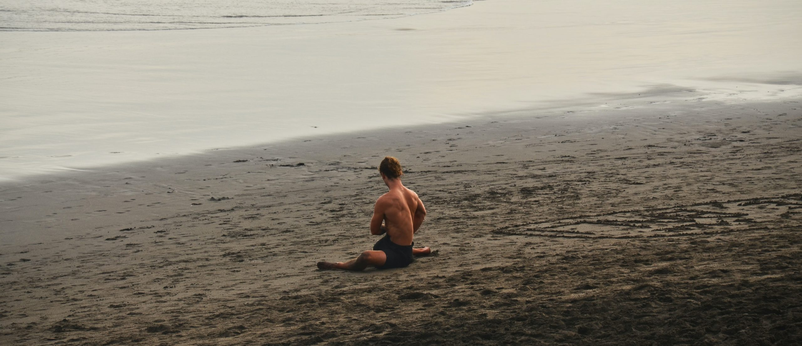 Muscular man stretching his back while on the beach