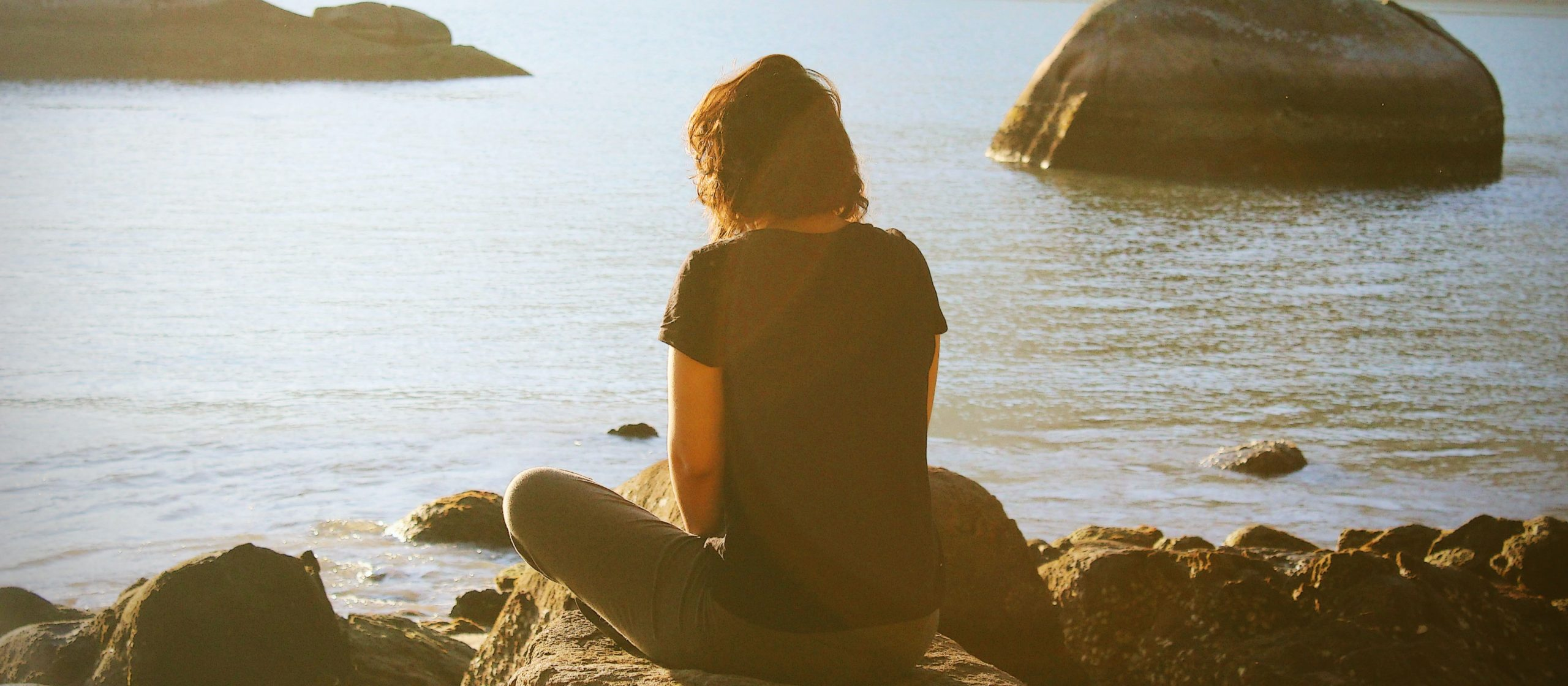 Woman meditating in front of water at sunset.