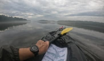 Man checking watch and a map while Navigating the Wisconsin River