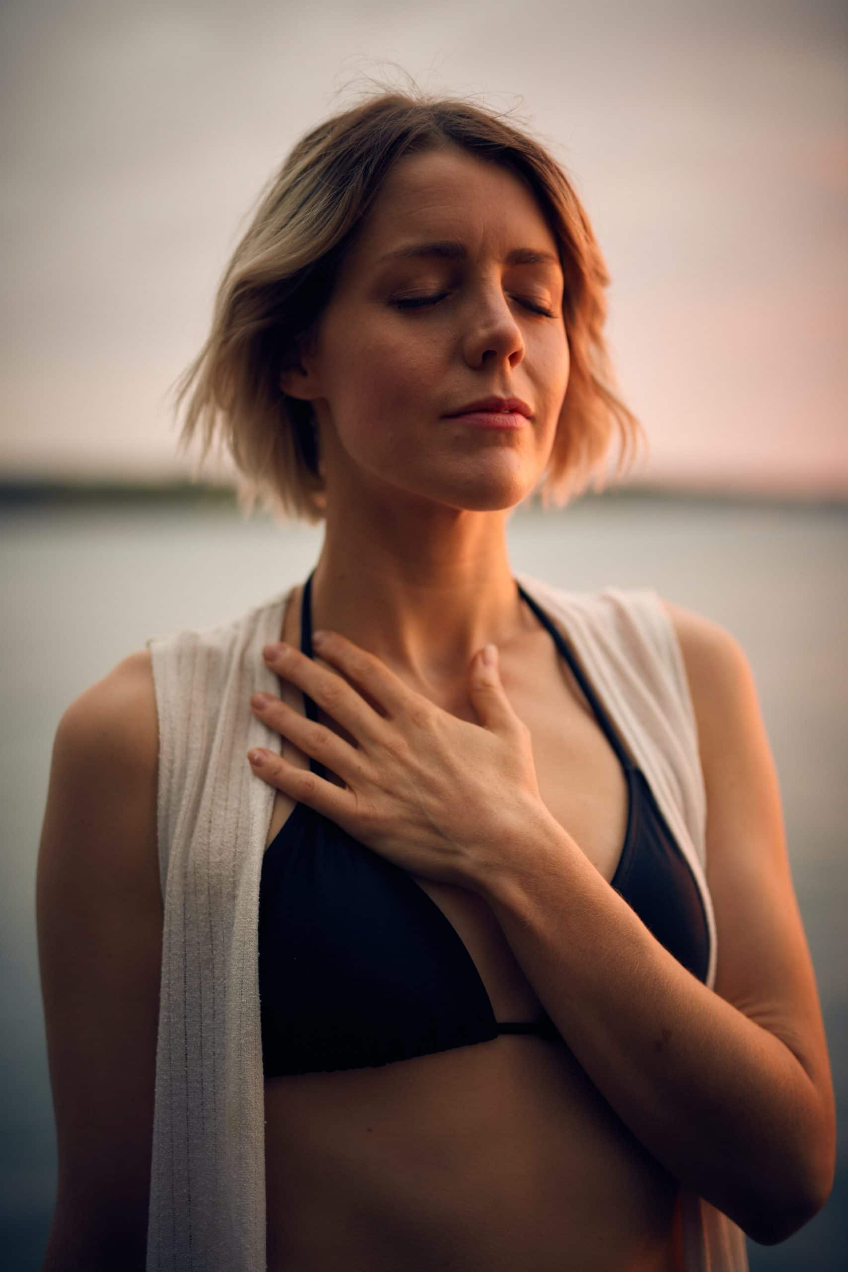 Woman practicing breathing exercises and mindfulness with hand over her heart in black swimsuit and white jacket