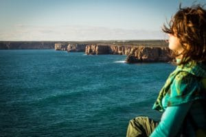 Woman practicing breathwork and meditation while sitting on a cliff overlooking the water and sunset
