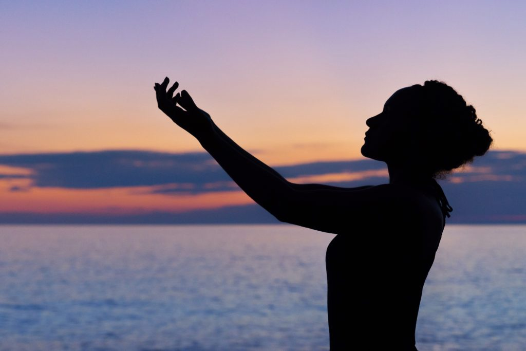 Indigenous Black Woman practicing mindfulness and raising arms over the ocean at sunset