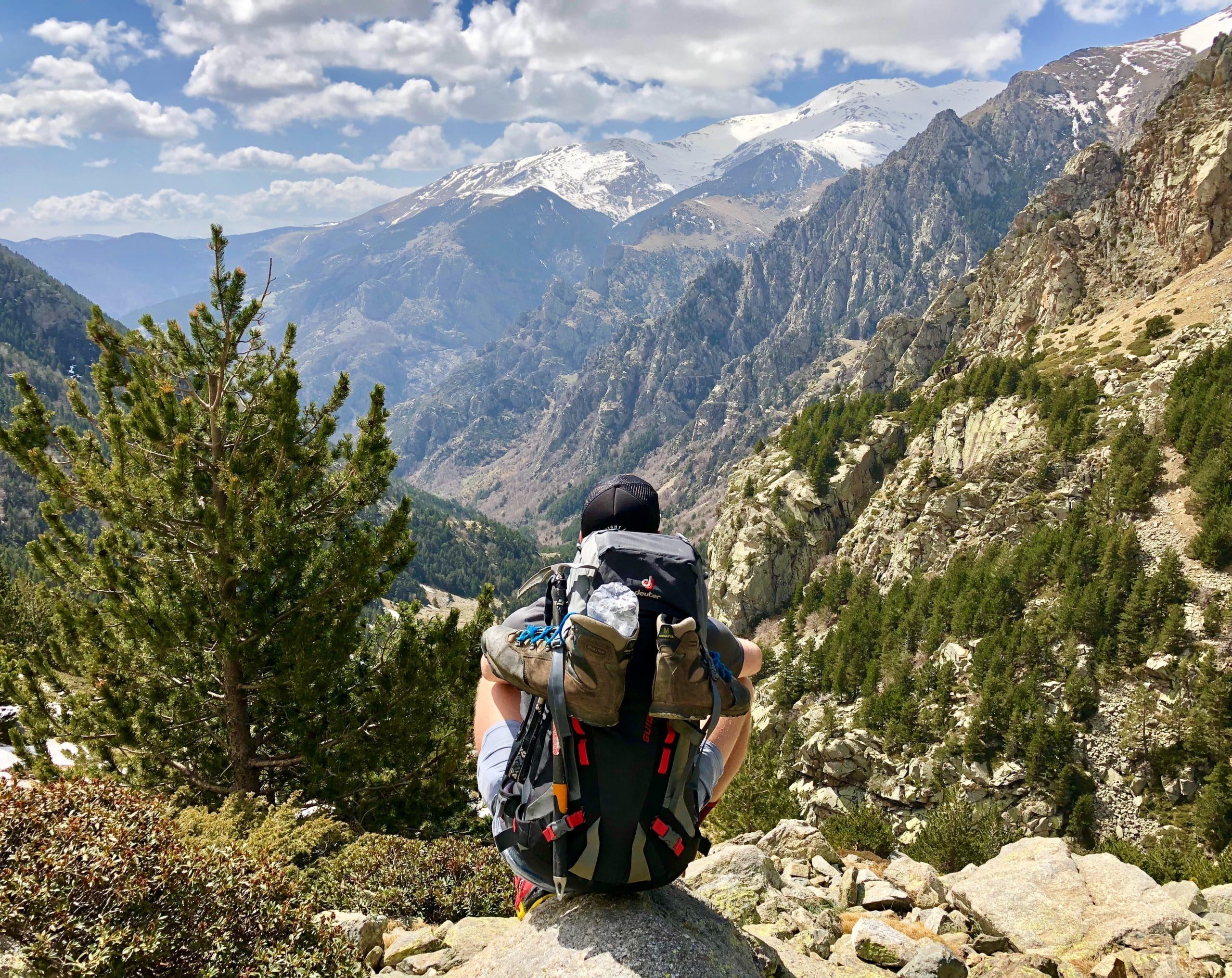 Man with a backpack practicing mindfulness while looking at a valley, trees, and mountains in the distance.